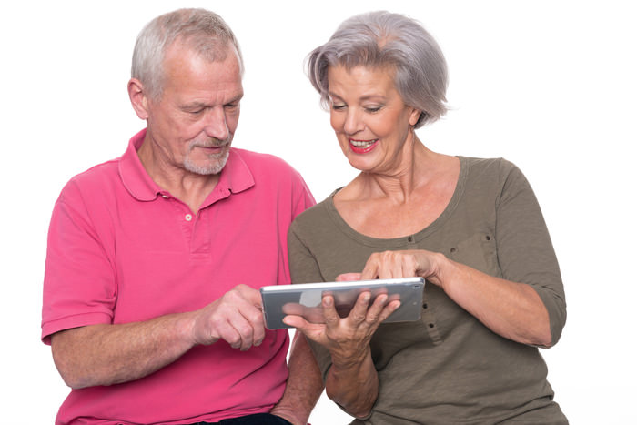 Senior couple with tablet computer in front of white background